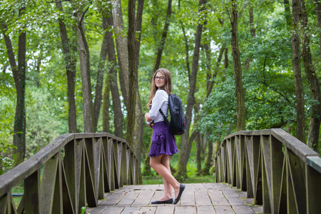Beautiful pretty blonde school girl child smiling with glasses, white shirt, purple skirt and black backpack standing on a wooden bridge in nature trees holding books happy back to school autumn