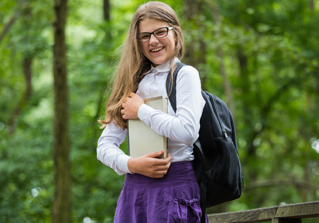 Beautiful pretty blonde school girl child cheerfully smiling with glasses, white shirt, purple skirt and black backpack standing on a wooden bridge in nature holding books happy back to school autumn
