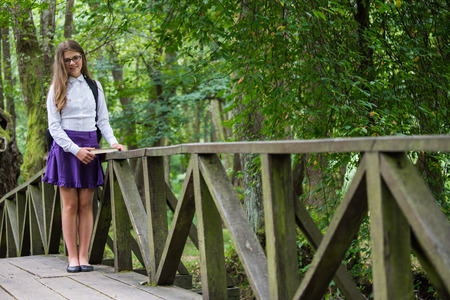 Beautiful pretty blonde school girl child cheerfully smiling with glasses, white shirt, purple skirt and black backpack standing on a wooden bridge in nature happy back to school autumn Zdjęcie Seryjne