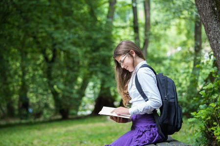 Pretty little blonde schoolgirl with backpack and long hair sitting on the bench in the nature park and reading a book ready to go back to school in the nature studying for exam happy in the autumn Zdjęcie Seryjne