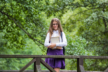 Beautiful pretty blonde school girl child smiling with glasses, white shirt, purple skirt and black backpack standing on a wooden bridge in nature holding books happy back to school autumn