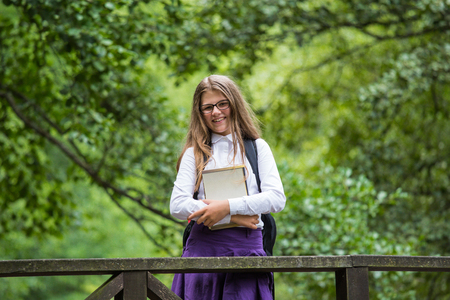 Beautiful pretty blonde school girl child cheerfully smiling with glasses, white shirt, purple skirt and black backpack standing on a wooden bridge in nature holding notes happy back to school autumn