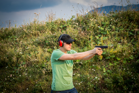 Military camp for young and professional special forces for soldiers to train shooting with firearms. You soldier policeman firing with gun glock pistol at the enemy criminal target with calmness Zdjęcie Seryjne