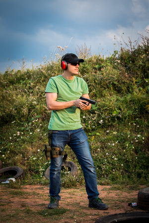 Young and handsome muscular caucasian guy with green shirt ready to shot and fire with gun glock pistol at the distant target in the military camo in nature with tire behind and professional equipment Zdjęcie Seryjne