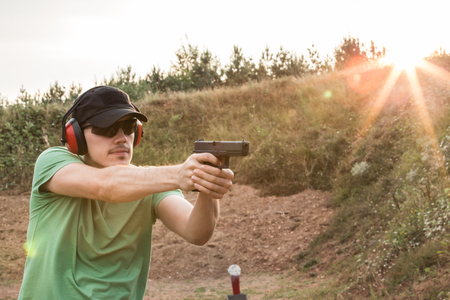 Outside training of the young and handsome muscular caucasian policeman or special force army soldier shooting bullets with gun glock pistol from firearms at the criminal enemy target in the nature