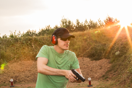 Caucasian military soldier or special force unit or policeman training on the field with the pistol ready to kill the enemy target criminal with gun glock pistol in his hands. Sunset in the nature Zdjęcie Seryjne