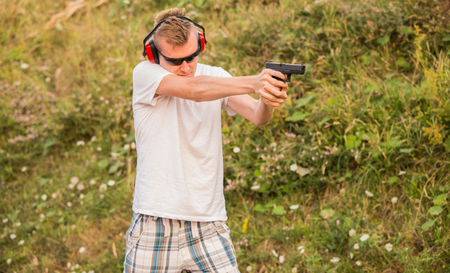 Young and strong caucasian blond guy firing bullets at the enemy target in the wilderness. Aiming to shoot with his gun glock pistol showing professional police skills in the nature.