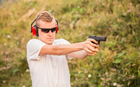 Handsome and young blond policeman professional army special force training guy shoot from fire arms with gun glock pistol in hands aiming at enemy target in the wild and violent criminal justice