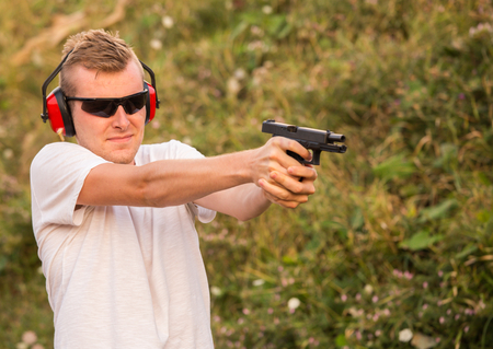 Young blonde handsome guy shooting from fire arms gun violent glock pistol aiming at the enemy target with firing bullets with black police sunglasses and sound blocker