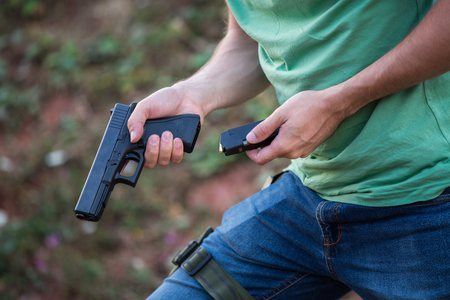 Guy with the pistol gun glock desert eagle changing bullets in the magazine to shot in the nature and having gun socket on the leg