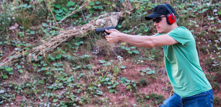 Young and handsome policeman special force muscle training with pistol glock and protective gear aiming to shot the enemy at target in the nature with black sunglasses. Fighting criminal violence Zdjęcie Seryjne
