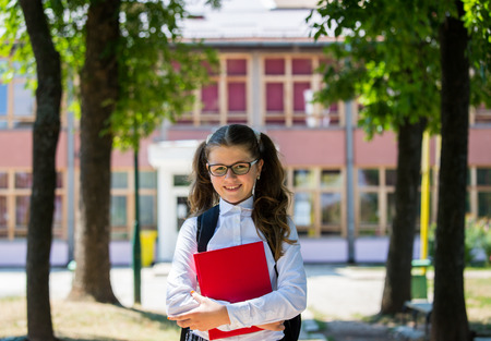 Young blue-haired girl with a backpack standing in front of school, beginning of school year, uniform, backpack, books, school, yard Zdjęcie Seryjne