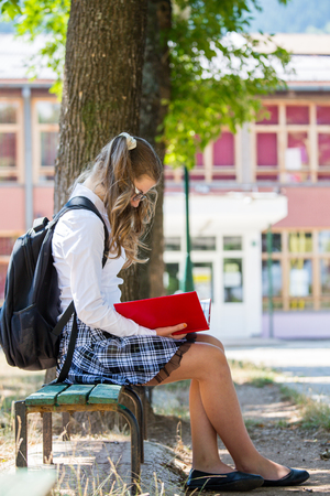 Young blue-haired girl with a backpack, sitting on the bench in front of a school, beginning of a school year, uniform, backpack, books, school, yard