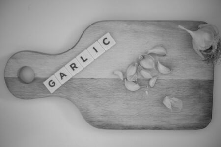 Garlic on wooden cutting board, shallots spread with word garlic written with letters Banque d'images