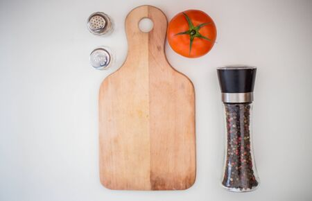 Kitchen plate for cutting, spices and tomatoes, pepper on white background, preparation for lunch Banque d'images