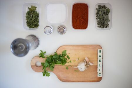 Preparing for lunch to eat on a white kitchen table with wooden cutting board, red pepper, green parsley, colorful pepper.Green salad and word garlic