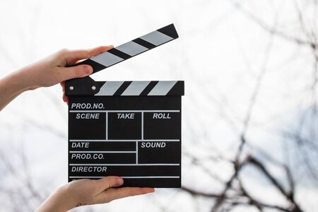 Female hands holding movie clapper isolated on white Standard-Bild