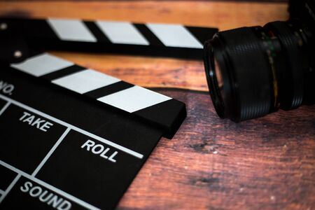 Movie clapper and old camera on a wooden background, movie shooting, film, screenplay, director Standard-Bild