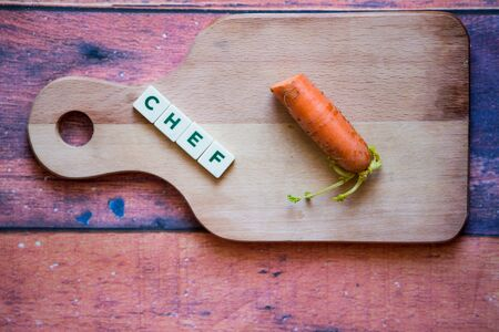 Word chef written with box letters. Wooden cutting board with orange fresh carrot on the wooden background.Healthy food and diet on the cutting board.