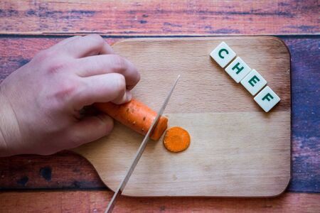 Chef is cutting carrot on a wooden cutting board with sharp knife and word chef written with box letters. Banque d'images