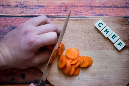 Chef is cutting carrot on a wooden cutting board with sharp knife and word chef written with box letters. Standard-Bild