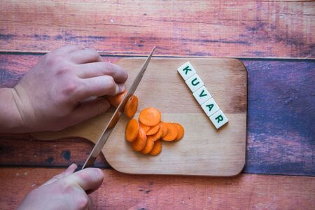 Chef is cutting carrot on a wooden cutting board with sharp knife and word for bosnian, serbian, croatian chef written with box letters.