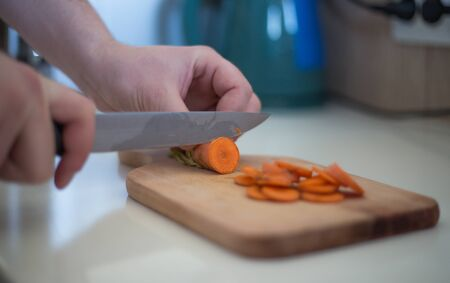 Chef is cutting carrot on a wooden cutting board with sharp knife