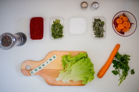 Preparing for lunch to eat on a white kitchen table with wooden cutting board, red pepper, green parsley, colorful pepper.Green salad and word cooking Standard-Bild