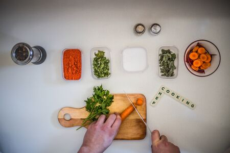 Preparing for lunch to eat on a white kitchen table with wooden cutting board, red pepper, green parsley, colorful pepper.Green salad and word cooking Banque d'images