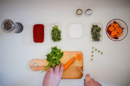 Preparing for lunch to eat on a white kitchen table with wooden cutting board, red pepper, green parsley, colorful pepper.Green salad and word chef