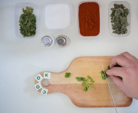Preparing for lunch to eat on a white kitchen table with wooden cutting board, red pepper, green parsley, colorful pepper.Green salad and word cook Standard-Bild