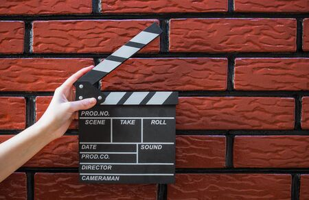 Clapper plates, women's hands and a movie clapper with a brick background Standard-Bild