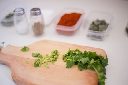 Green fresh parsley being prepared and cut for soup on the kitchen table and wooden cutting board with the seasonings aside salt and pepper for delicious meal food