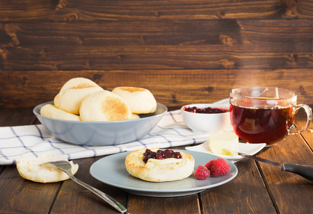 stile: English muffins with jam and butter on wooden background in rustic stile