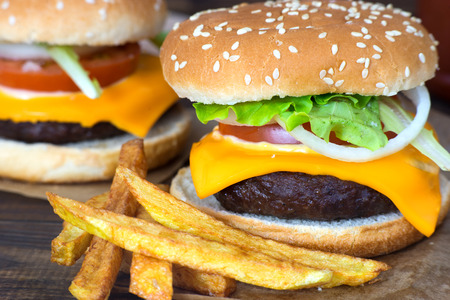 cheeseburgers: Close up of delicious homemade cheeseburgers and fries.