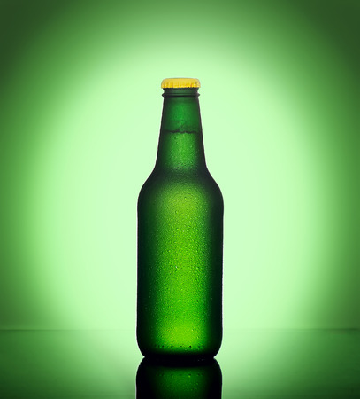 Bottle of cold beer with watter on green background with vignette Foto de archivo