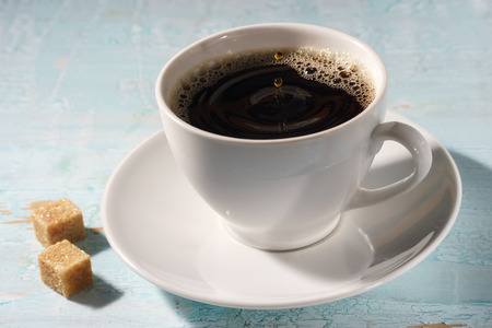 Cup of coffee in the early morning sun rays on blue vintage wooden table Stock Photo