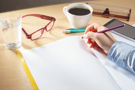 Woman hand writing in open blank notebook with glasses, cup of coffee, mobile phone on a desk