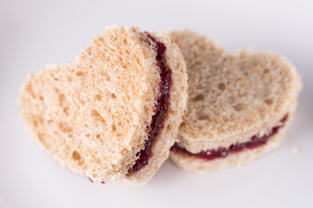 strawberry jam sandwich: Sweet sandwiches cut in heart shape with red plum jam for Valentines day