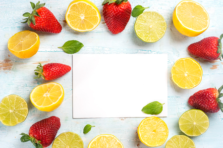 Lemons and strawberries on the blue wood