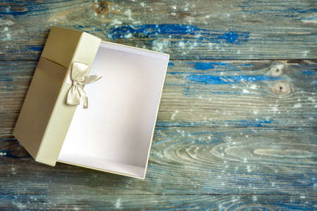 Open grey gift box with small bow on grey and blue wooden background Stockfoto