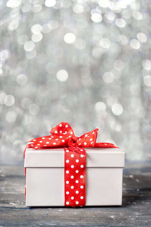 Vertical shot of grey gift box with red ribbon on glitter blured background