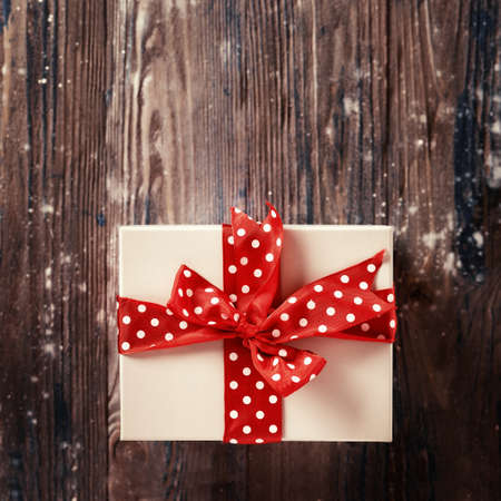 Top view of Christmas gift with big red bow on rustic background. Toning