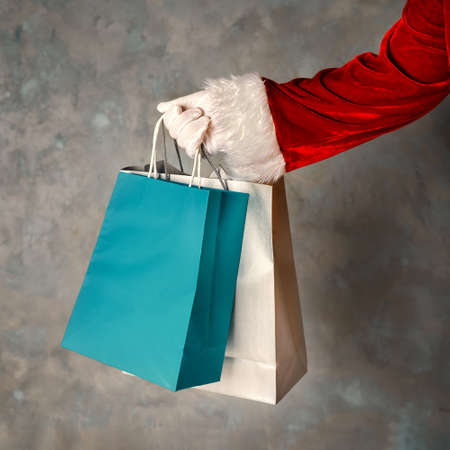 Close up of Santas hand holding a shopping bags. Square shot.