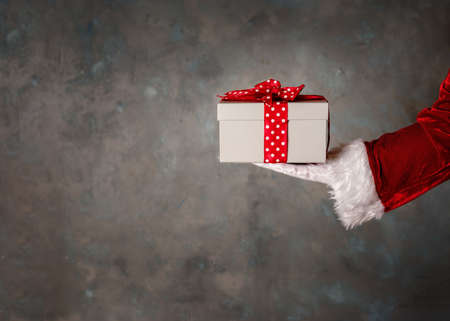 Santas hand holding a giftbox with red bow. Copy space. Stockfoto