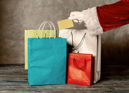 Close up of Santas hand holding a plastic card over the shopping bags shopping bags