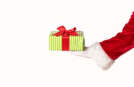 Santas hand holding a giftbox with red bow. Isolated on white
