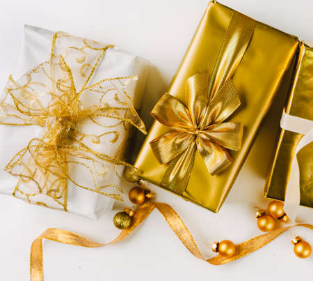 Topv view of golden Christmas presents on white wooden background