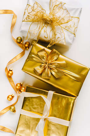 Topv view of golden Christmas gifts on white wooden background Stockfoto