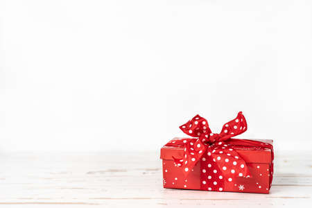 Red Christmas gift box with big red bow on white background. Copy space